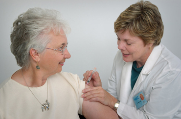 nurse giving middle aged woman a vaccination shot